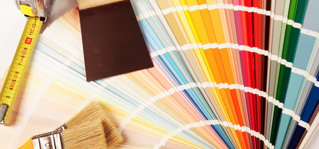 Une palette de couleurs avec des pinceaux et une spatule. Laquelle choisir pour les travaux de rénovation ? Image dui parle de rénovation, de travaux de décoration, la maison et la couleur.